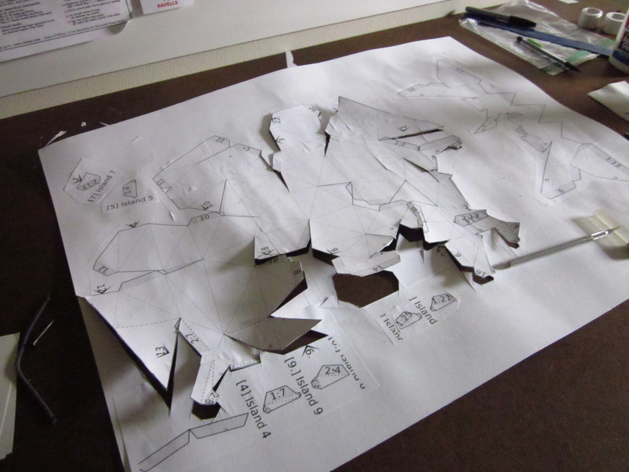 A sheet of posterboard lies on a brown surface, surrounded by implements of cutting. Jagged lines are cut in its wrinkled surface, and part of it peels up away from the brown.