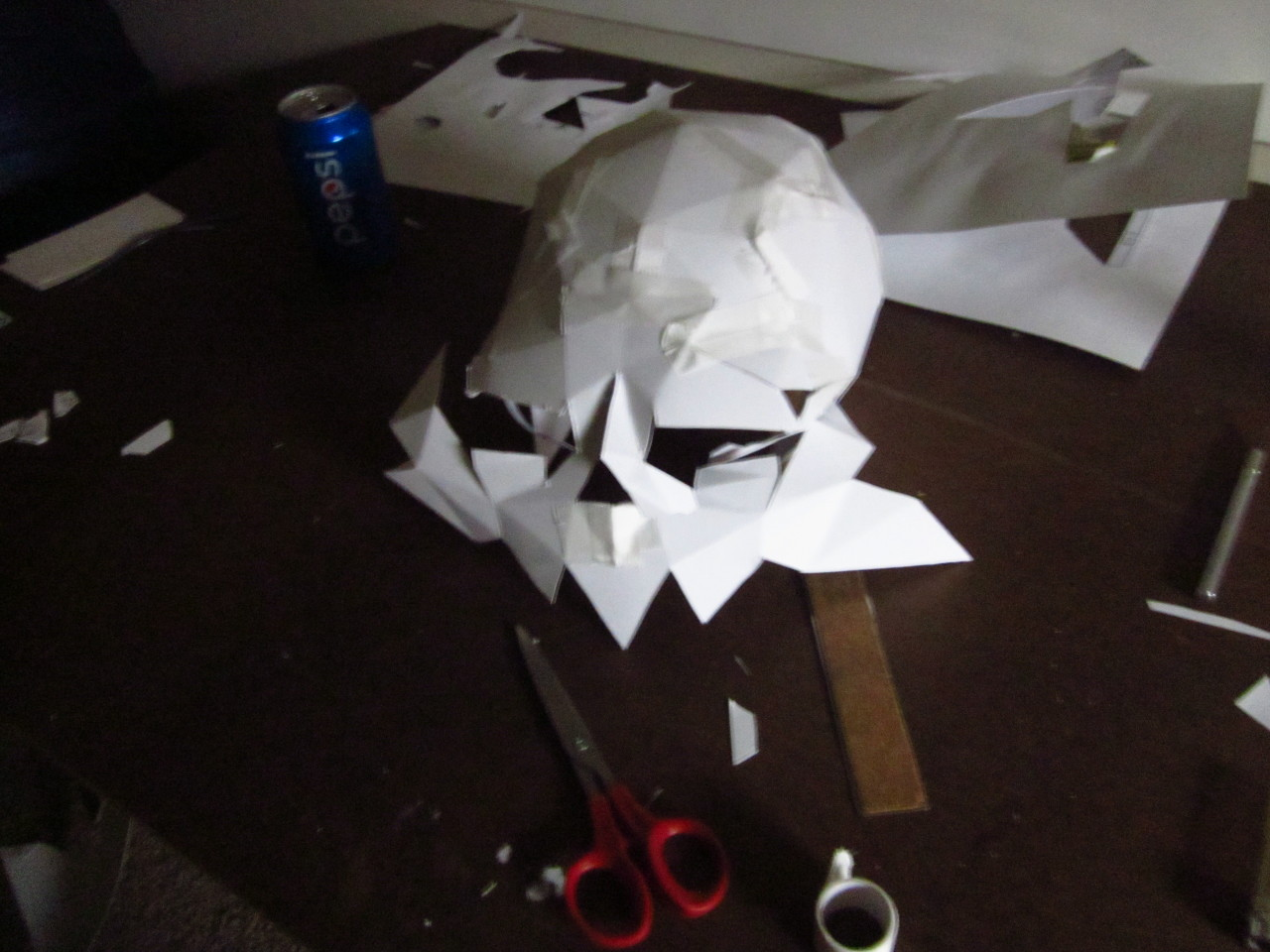 A papercraft skull sits on a brown desk, surrounded by rulers, scissors, knives, and tape. It is lit dramatically from one edge, and the face is shaped but not yet finally attached to the crown of the skull.