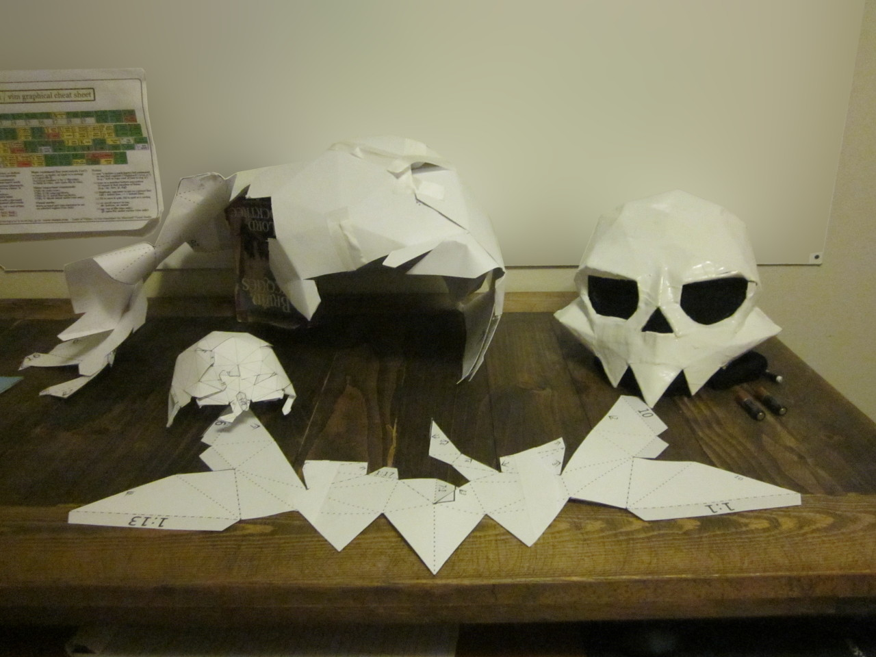 Three heaps of paper and one completed skull sit on a wooden table.