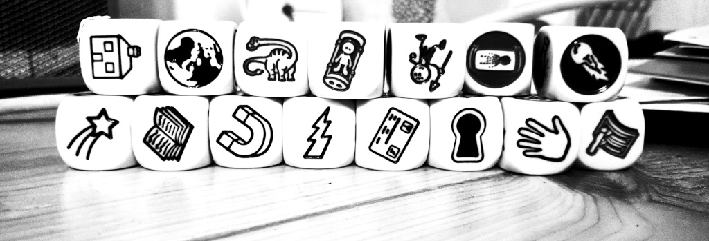 15 dice sit on a wooden table, stacked in two rows. The faces of the dice are icons representing concepts.